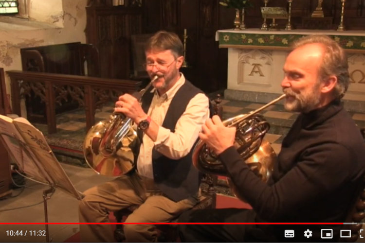 two gentkenen playing French Horns at St Wonnows